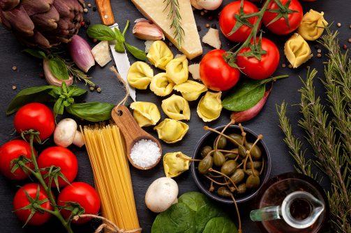 Séjour gastronomique : Ingrédients traditionels de la cuisine italienne avec légumes, huile d'olive, fromage, herbes et pâtes.