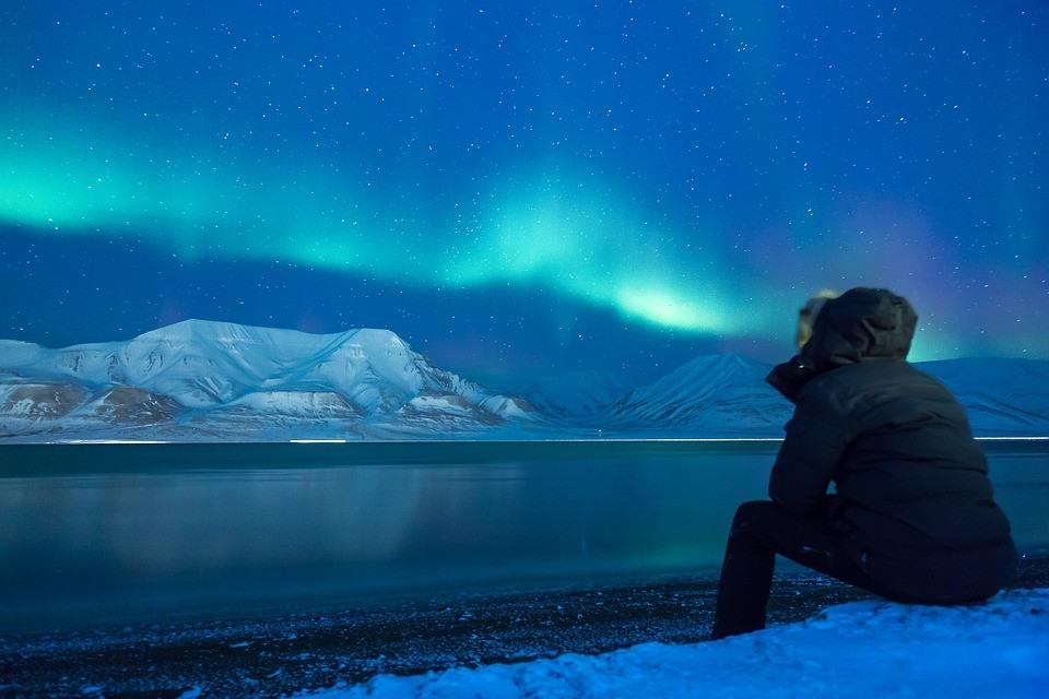 Jeune home admirant les aurores boréales en Islande